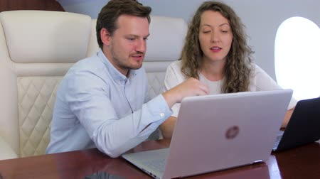 партнеры : Two analysts working on laptop on board of private jet. Caucasian businessman and businesswoman travel inside of business airplane cabin. Стоковые видеозаписи