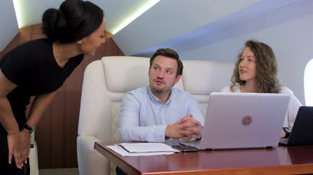 экипаж : Two analysts working on laptop on board of private jet. Biracial flight attendant offer her service to caucasian businessman and businesswoman traveling inside of business airplane cabin. Стоковые видеозаписи