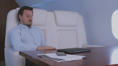 Stewardess taking care of passenger. Biracial flight attendant covering tired after hard laptop work sleepy businessman with blanket during trip on private business jet.