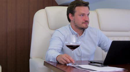 first class : Work on laptop on board of private jet. Businessman comfortably discussing with partner while drinking wine inside of business airplane cabin.