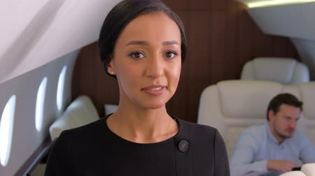 Businesswoman in private jet. Well dressed, confident female biracial entrepreneur smiling inside of business airplane cabin.