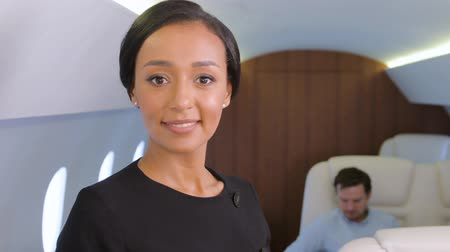 aircraft cabin : Stewardess portrait in private jet. Female biracial flight attendant smiling inside of business airplane cabin with passengers on background.