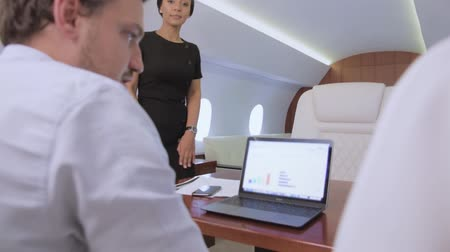 Two analysts working on laptop on board of private jet. Biracial flight attendant offer her service to caucasian businessman and businesswoman traveling inside of business airplane cabin. Stock Footage