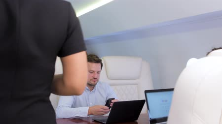 Work on laptop on board of private jet. Biracial flight attendant bringing glass of wine for caucasian businessman and businesswoman travel inside of business airplane cabin.