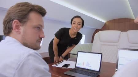 Two analysts working on laptop on board of private jet. Biracial flight attendant offer her service to caucasian businessman and businesswoman traveling inside of business airplane cabin. Stock mozgókép