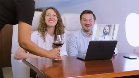 first class : Making video conference call with colleague on laptop HUD hologram on board of private jet. Flight attendant offer glass of wine for caucasian businessman and businesswoman inside business airplane