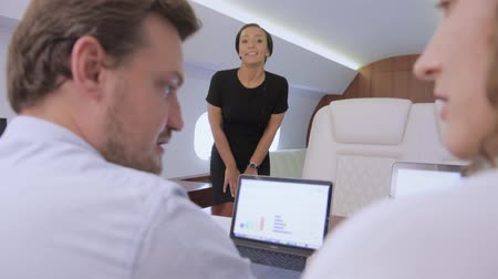 attendant : Two analysts working on laptop on board of private jet. Biracial flight attendant offer her service to caucasian businessman and businesswoman traveling inside of business airplane cabin. Stock Footage