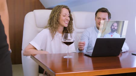 attendant : Making video conference call with colleague on laptop HUD hologram on board of private jet. Flight attendant offer glass of wine for caucasian businessman and businesswoman inside business airplane