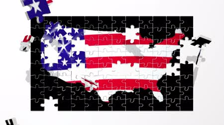 jigsaw : Puzzle pieces fly in and form a map of the USA with a billowing stars and stripes stenciled behind the outline of the country. Stock Footage