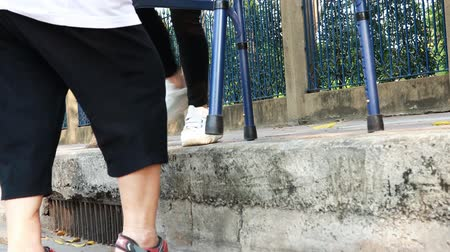 crosswalk : Asian mother and daughter help, care, support outdoor senior grandmother after cross the road, barrier from footpath, sidewalk is tall, different level area,elderly with walker, leg pain, lifestyle problem
