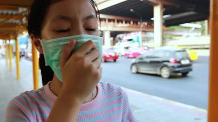 tosse : Tired asian child girl sneezing,cough wearing hygienic mask,air pollution problems,respiratory disease,air contamination,inhaling toxic fumes,PM 2.5,allergy to dust,bad smell from cars in city street