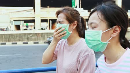 tosse : Stressed asian mother and daughter with hygienic mask walking outdoor,allergy to dust,pollution,dirty air,PM 2.5,health care,virus protection,respiratory disease,air contamination,inhaling toxic air