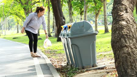 consciência : Asian woman picking up litter from the floor into the trash can,female people picking up garbage plastic bag on the grass at park,putting into public rubbish bin,helping to clean the environment Stock Footage