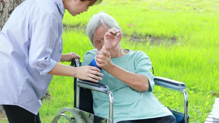 söylemek : Injured asian senior woman wearing elbow support suffering from sore muscle,elbow joint arm pain,female caregiver do not intend to massage hard,unhappy elderly with elbow protector pads feeling hurt