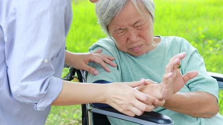 söylemek : Injured asian senior woman wearing elbow support suffering from sore muscle, elbow joint arm pain, female caregiver do not intend to massage hard, unhappy elderly with elbow protector pads feeling hurt