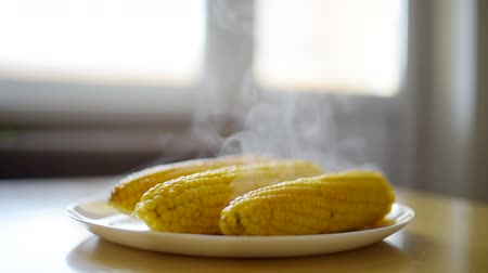Sweet yellow boiled hot steam corn on the table in white plate Stok Video