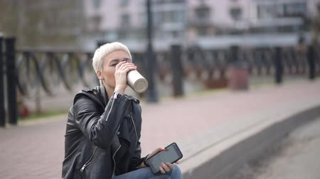 girl sits on the street, smiles and drinks coffee from a thermos