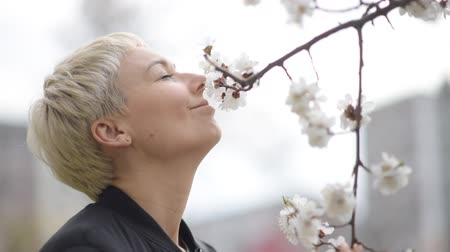 The girl sniffs a flowering cherry tree in early spring. Stok Video