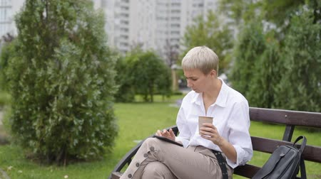 Coffee break. Business woman sitting in the park on a bench, working with a phone