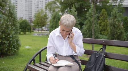 mezítláb : Coffee break. Business woman sitting in the park on a bench, working with a phone