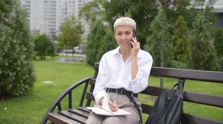 one by one : Coffee break. Business woman sitting in the park on a bench, working with a phone