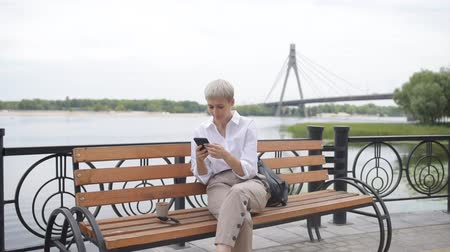 Coffee break. Business woman sitting in the park on a bench, looking in the phone and smile
