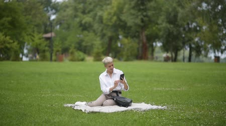 beautiful woman blonde reads a book on the grass in the park