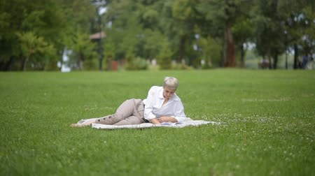 livros didáticos : beautiful woman blonde reads a book on the grass in the park