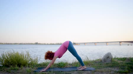 pilates : Girl with red hair relaxing while meditating and doing yoga exercise in the beautiful nature beside river