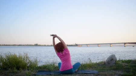 Girl with red hair relaxing while meditating and doing yoga exercise in the beautiful nature beside river