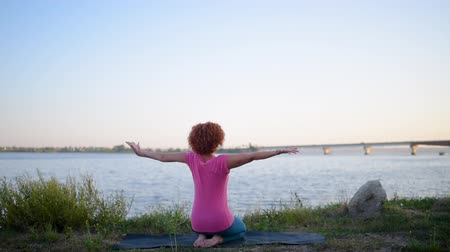 flexibilidade : Girl with red hair relaxing while meditating and doing yoga exercise in the beautiful nature beside river