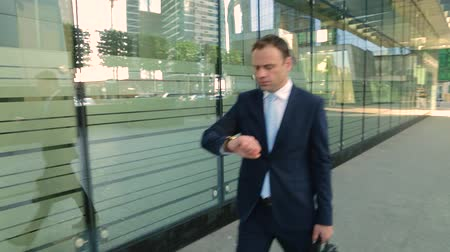 честолюбие : Businessman in a suit in a hurry, hi is late, looking at the watch. Steadicam shot. Стоковые видеозаписи