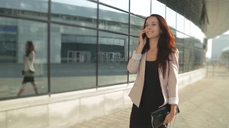 healthy office : Pretty girl walking and talking on the phone in the sun. Steadicam shot. Stock Footage