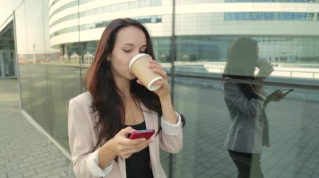 кружка : Pretty girl walking and using app on smartphone drinking coffee. Steadicam shot.