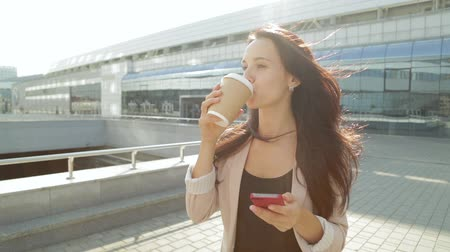 кружка : Pretty girl walking and using app on smartphone drinking coffee in the sun. Steadicam shot. Стоковые видеозаписи