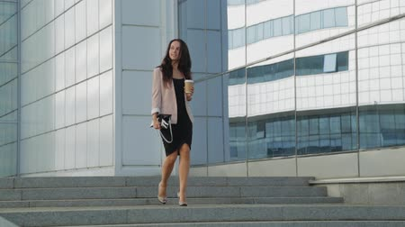 pięta : Pretty girl with cup of coffee walking in high heels down the street. Steadicam shot.
