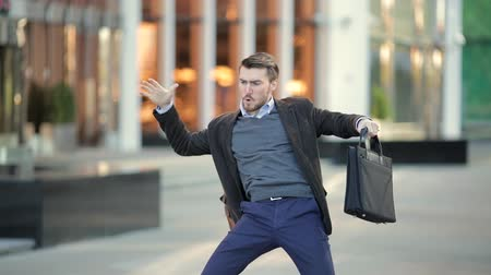 volný čas : Attractive man with a beard and briefcase dancing in the street