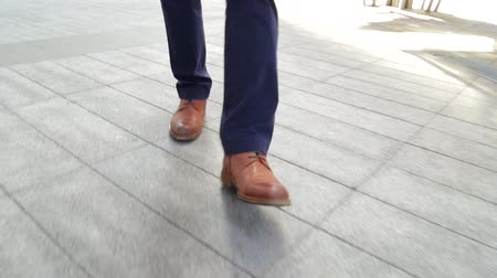 healthy office : Close crop of mans feet walking in city (steadicam shot) Stock Footage