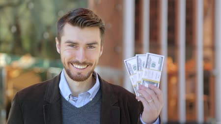 премия : Happy attractive man holding in his hand bundles of money cash dollars