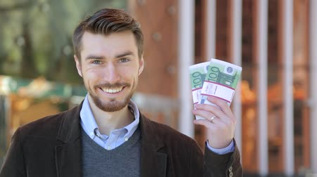 euro : Happy attractive man holding in his hand bundles of money cash Euro
