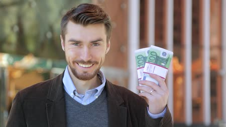 bajnok : Happy attractive man holding in his hand bundles of money cash Euro