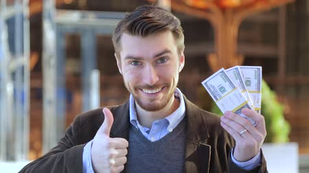 vencedor : Happy man holding in his hand bundles of money cash dollars and showing thumbs up