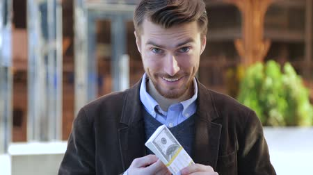премия : Attractive man leafing through a bundle of dollars, looking at camera and smiling