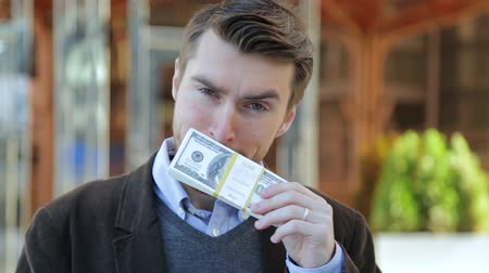 bajnok : Attractive man leafing through a bundle of dollars, smelling cash, looking at camera and smiling