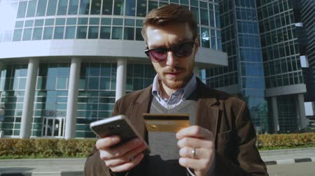 číslo : Attractive man using online banking on smartphone with credit card in the street