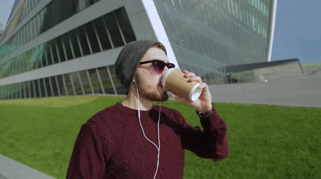 chapéu : Handsome hipster listening to music in smartphone headphones and drinking coffee from paper sup, walking and dancing