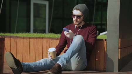 hippie : Handsome hipster listening to music in smartphone headphones and drinking coffee from paper sup