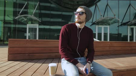 hippie : Handsome hipster listening to music in smartphone headphones on wooden bench Stock Footage