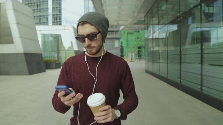 hippie : Handsome hipster using app and listening to music in smartphone headphones, drinking coffee and walking