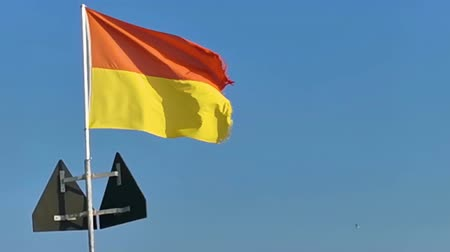 closeup of a red with yellow waving flag, supervised bathing area at the beach of domburg, the netherlands Dostupné videozáznamy